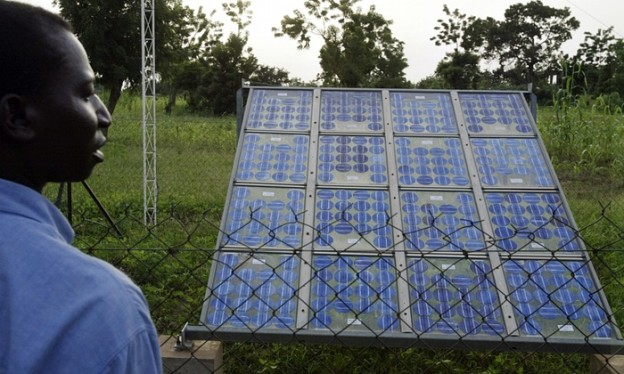 Vision of the future … a resident of Tanghin-Dassouri, near Ouagadougou in central Burkina Faso, looks at a solar panel. Photograph: Issouf Sanogo/AFP/Getty Images