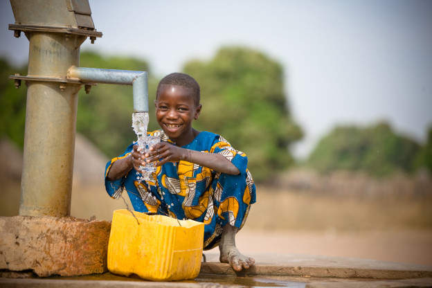 Young boy at water pump / well. Samba Diallo, age 7. Sansacoto Village.
